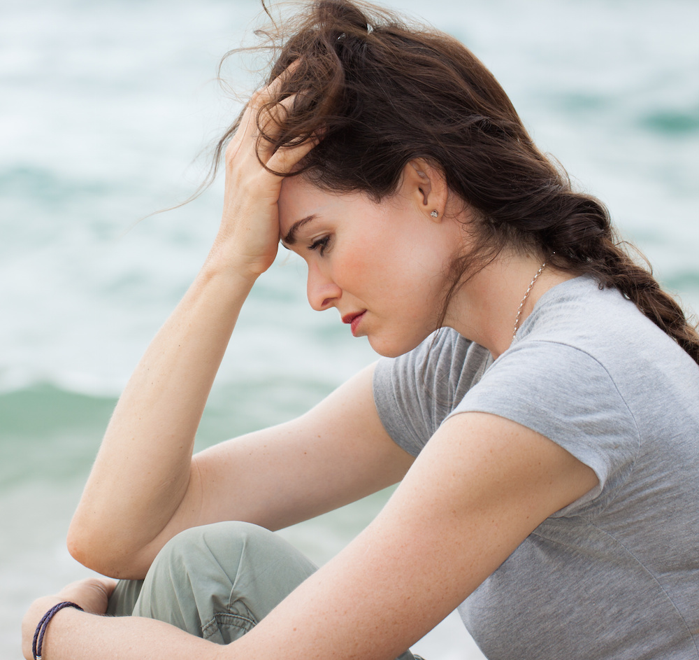 Close-up of a sad and depressed woman deep in though outdoors.