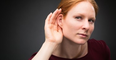 A curious young woman listens to something interesting with a hand behind her ear.